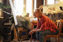 Woman Admiring Painting In Workshop
