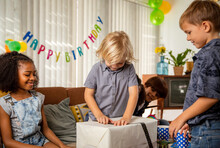 Boy Celebrating Birthday At Home With His Friends - Unwrapping A Birthday Gift