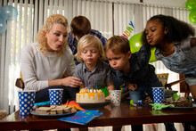 Boy Celebrating Birthday At Home With His Friends - Blowing The Candles