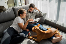 Young Couple Relaxing And Reading In Living Room With Pets