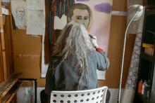 Artist Woman Painting A Male Portrait Back View