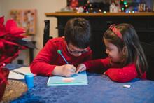 Siblings Writing To Santa Claus For Christmas