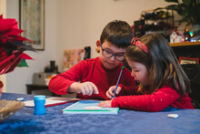 Brother Helping Little Sister Writing To Santa Claus