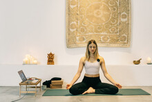 Female Yoga Instructor Teaching Online Meditation Class During Lockdown