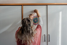Woman Hanging A Mandala Painting At Room