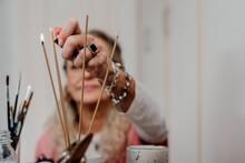 Senior Woman Lighting Incense At Home