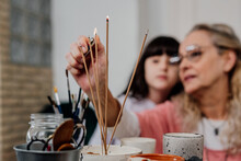 Grandmother And Grandaughter Burning Incense To Practice Meditation