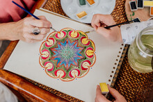 Close-up Of Grandmother Painting Mandala With Her Granddaughter At Room