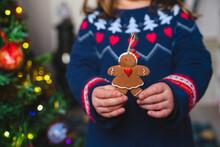 Little Girl Holding Gingerbread Woman Ornament