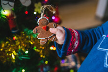 Placing Gingerbread Woman Ornament On Christmas Tree