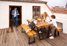 Content Family Having Breakfast Together On Terrace