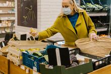 Close-up Of Senior Woman Picking Lemons In Bulk At Market