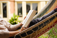 Young Woman Lying In A Hammock Reading A Book
