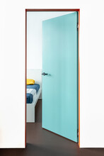 Half Open Bedroom Blue / Green Door With An Orange Frame And White Wall