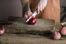 Anonymous Woman Cutting Red Onion On Wooden Board