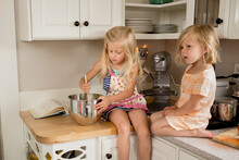 Sisters Stir Batter On Kitchen Counter