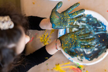 Children's Hands Mixing Blue Paint With Gold Stars For Crafts