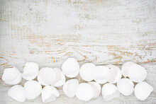 Lots Of Broken White Eggshells On A Light Wooden Background. Copy Space