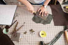 Artisan Trims Leather With Rotary Tool At Work Table