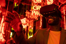 Content Black Man In VR Goggles In Room With Neon Lights