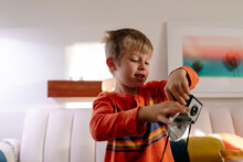 Cute Boy Figuring How To Use An Old Camera In The Living Room At Home