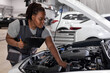 car service, job and profession concept. young african female worker in gray uniform with clipboard and pen writing over auto repair shop on background