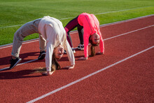 Flexible Girls Gymnasts Stand In Crab Position On Athletics Track, Flexibility