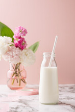 A Bottle Of Milk On Marble Table On Pink Background With Pink And White Flower Bouquet, Bright And Pastel Drink Composition