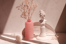 Retro Interior Composition With Sunlight And Shadows In Minimalist Style. Decorative Plate, Plaster Girl Face And Pink Vase With Gypsophila Flowers On A Light Beige Background.
