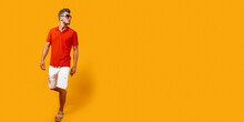 Full Length Portrait Of A Handsome Man In Shorts And Red Shirt Walking And Looking Sideway Isolated On Yellow Background. Summertime Concept