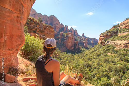 Canvas-taulu Woman looking down into a green canyon in the desert