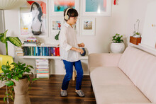 Teen Boy Dancing And Singing By Colorful  Books And Wall Gallery