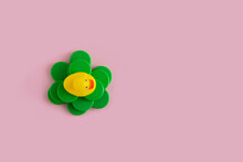 Yellow Rubber Duck On A Green Plastic Waste Pollution Island  On A Pink Pastel Background. Polluted Environments. Flat Lay View.