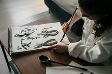 Young Woman Writing Japanese Kanji Characters With A Brush And Ink