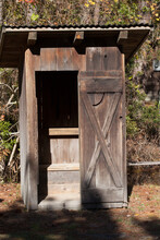 An Old Wooden Outhouse In The Sunshine