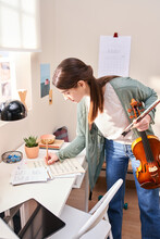 Violinist Making Notes In Sheet Music.