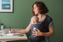 Mother With Baby In Wrap Carrier Working From Home
