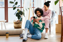 Multiracial Couple Using Smartphone During Relocation