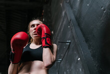 Confident Sportswoman In Boxing Gloves Training In Gym