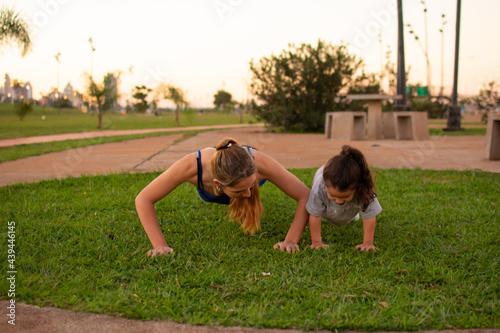 Canvas madre e hija haciendo flexiones de brazos en un parque al aire libre