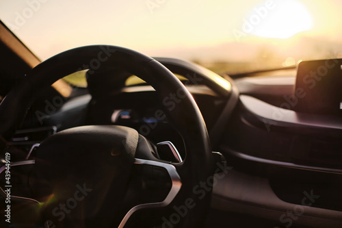 photograph of steering wheel and console of a car riding on the freeway in sunrise .shot with vary shallow focusing that keep most of photograph out of focus blurred