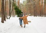 happy couple walking through the forest with christmas tree
