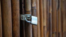 Brown Bamboo Door Or Fence, With Locked Gray Padlock. Focus Selected