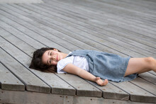 Cute, Little Girl Is Lying On A Wood Stairs.