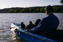 Anonymous Fisherman Sitting On Boat In River