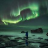 Man watching northern lights at uttakleiv beach in Norway