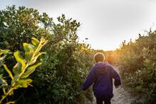 Boy Follows His Brother Down A Sandy Path