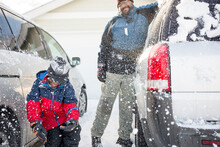 Father And Son Clean Snow Off Suv