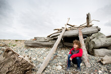 Boy Crouches In Driftwood Fort On Rocky Beach