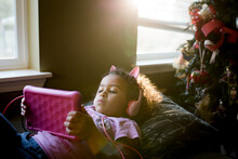 Girl With Headphones Lays On Couch Looking At A Pink Tablet